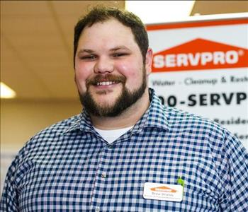 headshot of male smiling with dark hair in front of a SERVPRO sign